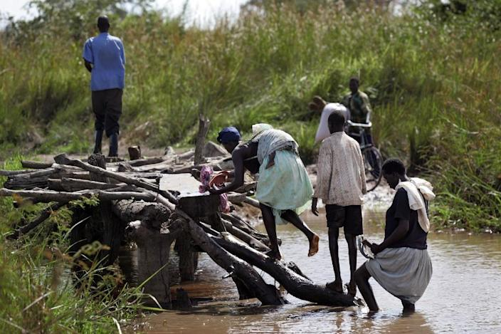 Ugandan villagers climb a wooden bridge that was partially destroyed by major floods that hit the country in 2007 (AFP Photo/Roberto Schmidt)