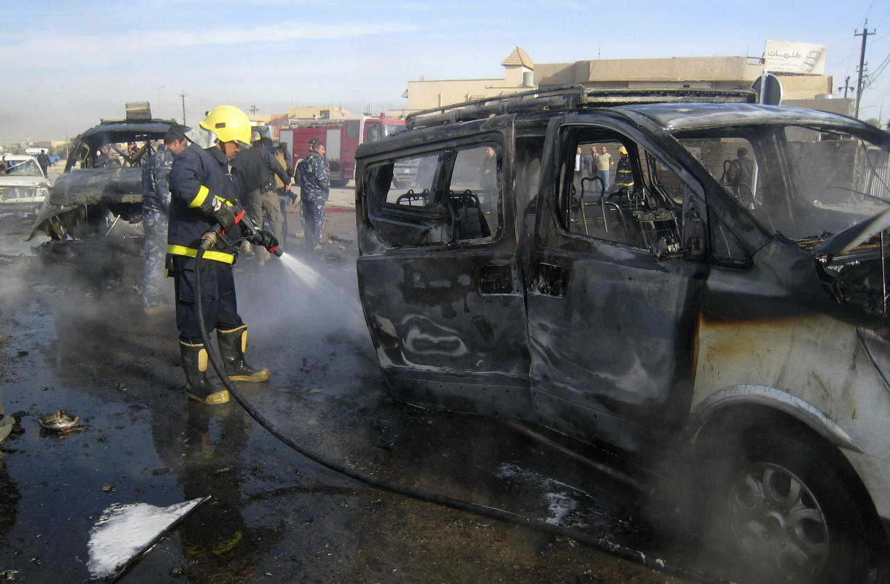 An Iraqi firefighter hoses down a burned bus after a car bomb attack in Kirkuk, 290 kilometers (180 miles) north of Baghdad, Iraq, Thursday, Feb. 23, 2012. A rapid series of attacks spread over a wide swath of Iraqi territory killed and injured dozens of Iraqis on Thursday, targeting mostly security forces. (AP Photo/Emad Matti)