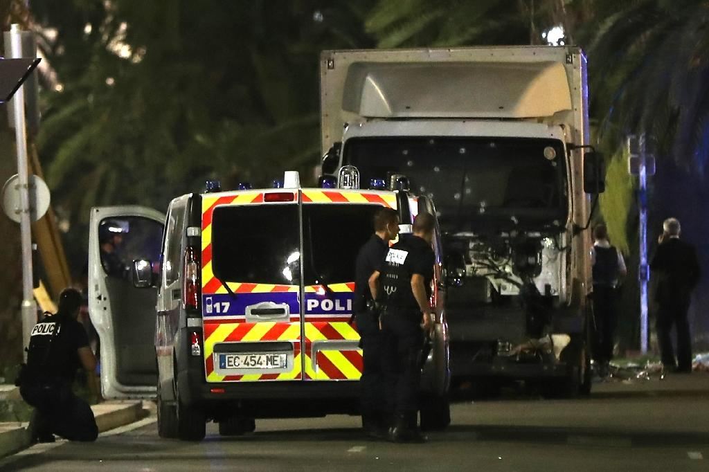 Police stand near a truck that ploughed into a crowd leaving a fireworks display in the French Riviera town of Nice on July 14, 2016 (AFP Photo/VALERY HACHE)