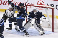 Winnipeg Jets' Dmitry Kulikov (7) and Los Angeles Kings' Adrian Kempe (9) fight for position in front of goaltender Connor Hellebuyck (37) during the first period of an NHL hockey game Tuesday, Oct. 22, 2019, in Winnipeg, Manitoba. (Fred Greenslade/The Canadian Press via AP)