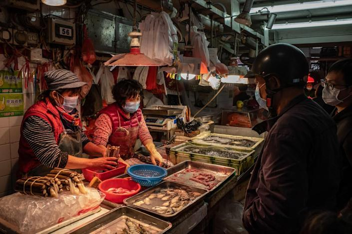 Two people in masks handle seafood that fills trays atop a table. Two others peruse the goods.