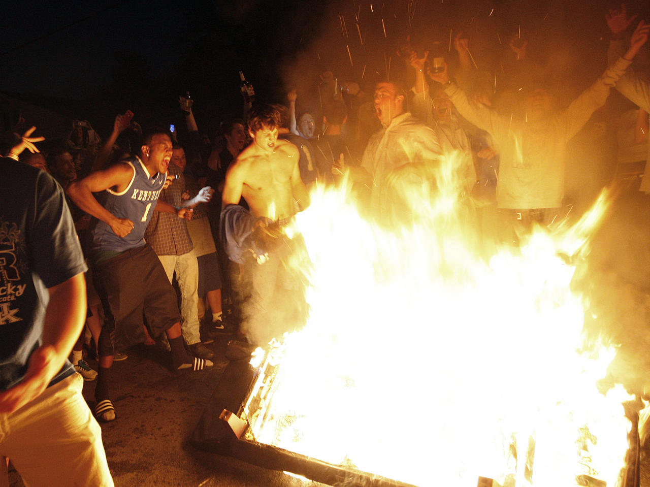 Kentucky fans dance around a fire on State Street as they celebrate Kentucky's 69-61 win over Louisville in an NCAA Final Four semifinal college basketball tournament game, Saturday, March 31, 2012, in Lexington, Ky. (AP Photo/The Courier-Journal, Amy Wallot) NO SALES; MAGS OUT; NO ARCHIVE; MANDATORY CREDIT