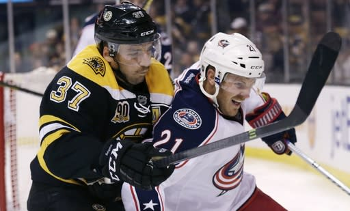 Boston Bruins center Patrice Bergeron (37) and Columbus Blue Jackets defenseman James Wisniewski (21) chase after the puck during the second period of an NHL hockey game, in Boston, Thursday, Nov. 14, 2013. (AP Photo/Charles Krupa)