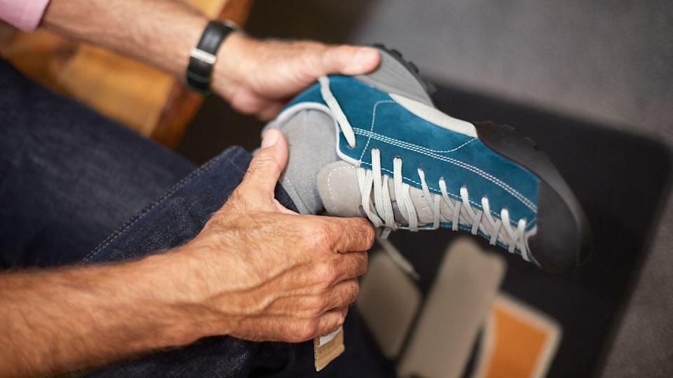 Unrecognizable senior man in sports and outdoor equipment store choosing to buy hiking shoes.