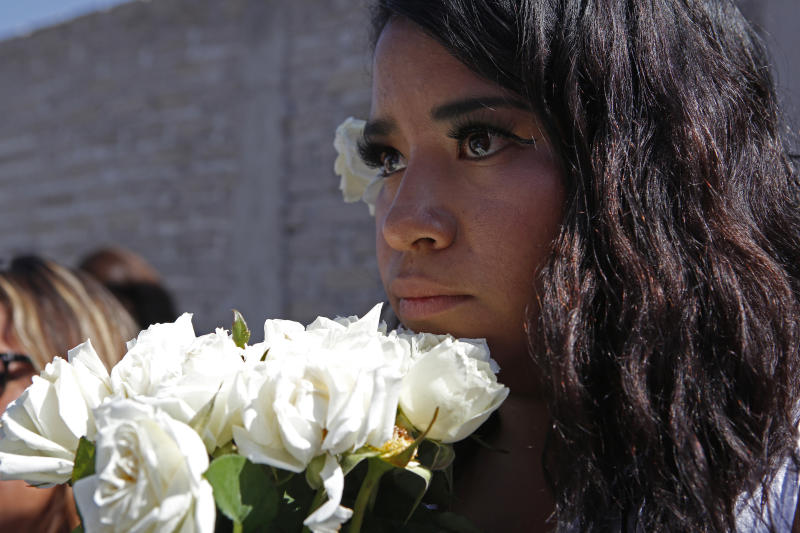"""An activist from the """"Women from the Periphery for the Periphery Collective"""" holds flowers where the body of 2-year-old Samantha was found dead outside her home in June, during a caravan to protest femicide in Ecatepec, Mexico, Sunday, Oct. 6, 2019. The collective of activists and the relatives of murdered females visited four sites where females were found dead in Ecatepec, in the state of Mexico where authorities declared in 2015 an alert concerning gender violence against women. (AP Photo/Ginnette Riquelme)"""