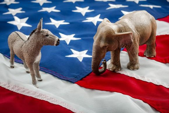 A Democrat donkey and a Republican elephant having a stare-down while standing on the American flag.