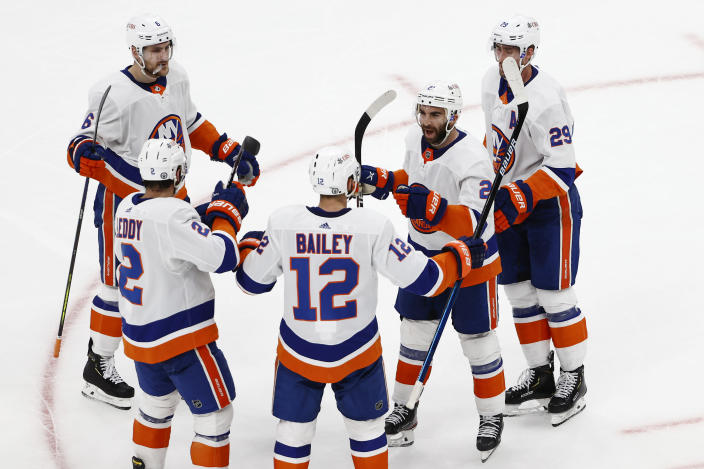 New York Islanders' Josh Bailey (12) is congratulated by teammates, including Kyle Palmieri (21), after scoring against the Boston Bruins in the second period of Game 2 during an NHL hockey second-round playoff series, Monday, May 31, 2021, in Boston. (AP Photo/Winslow Townson)