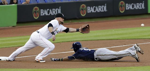 Milwaukee Brewers' Jean Segura (9) slides safely into third base as Miami Marlins third baseman Casey McGehee, left, is unable to reach the ball in the first inning of a baseball game in Miami, Friday, May 23, 2014. (AP Photo/Alan Diaz)
