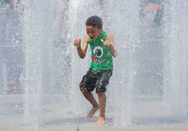 David Adejor, six, beats the heat as he runs through water fountains in Montreal on Sunday.  (Graham Hughes/The Canadian Press - image credit)
