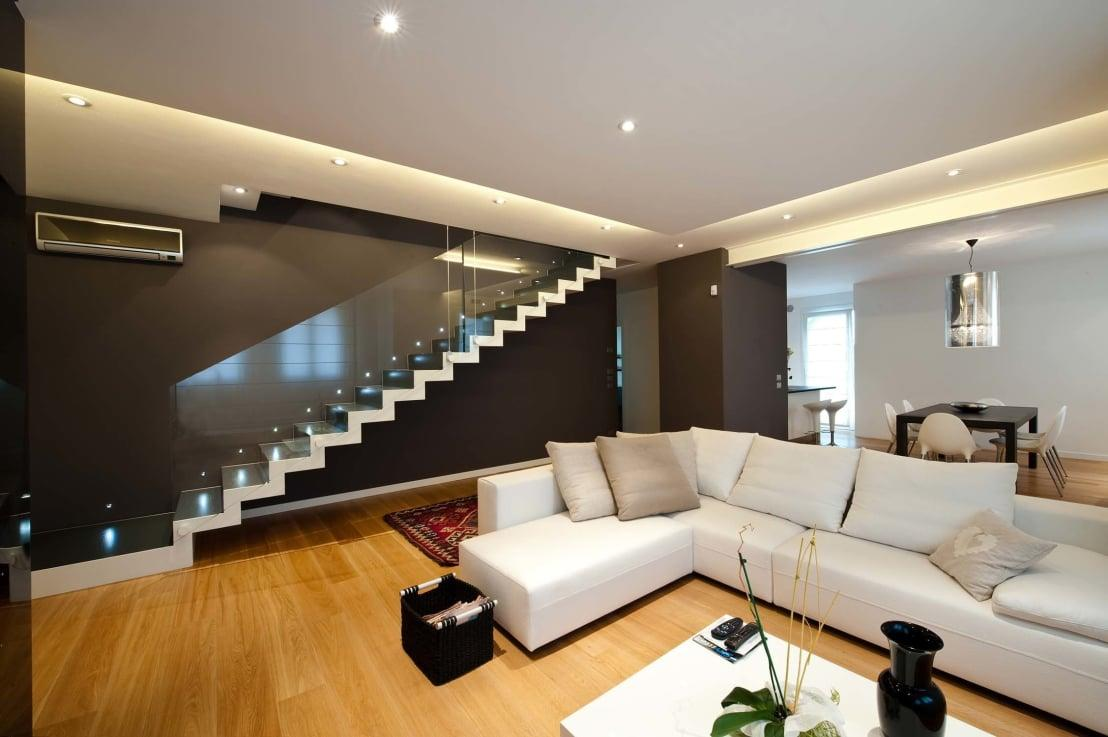 """<p>In this minimalist living room, this gypsum lacquered false ceiling adorns the roof along the height of the stylishly lit oak wood and enticing glass<a rel=""""nofollow"""" href=""""https://www.homify.co.uk/rooms/stairs"""">stairway</a>.</p>  Credits: homify / SANSON ARCHITETTI"""