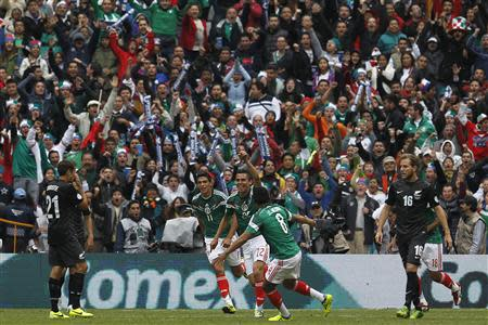 Mexico's Paul Aguilar celebrates his goal with Raul Jimenez and Juan Medina during their 2014 World Cup qualifying playoff first leg soccer match against New Zealand at Azteca stadium in Mexico City