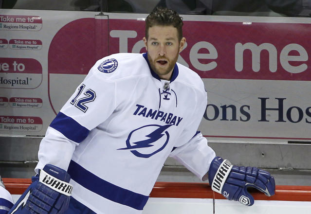 This Feb. 4, 2014 photo, Tampa Bay Lightning left wing Ryan Malone (12) stretches before an NHL hockey game against the Minnesota Wild in St. Paul, Minn. Malone was charged Saturday with DUI and possession of cocaine after a traffic stop, police said. An officer saw Malone's SUV strike a curb after making a left turn from the center lane early Saturday, said Tampa Police Lt. Paul Lusczynski. After being pulled over, Malone got out of his vehicle, and the officer smelled alcohol on his breath, Lusczynski said. According to the police report, the officer also found 1.3 grams of cocaine in one of Malone's pockets. Malone was released from the Hillsborough County jail on $2,500 bond. (AP Photo/Ann Heisenfelt)