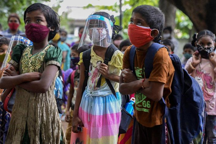 Colorfully clothed children wear masks and carry backpacks