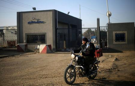 A Palestinian rides a motorcycle outside Kerem Shalom, the main passage point for goods entering Gaza, after it was shut down by Israel, in the southern Gaza Strip January 14, 2018. REUTERS/Ibraheem Abu Mustafa