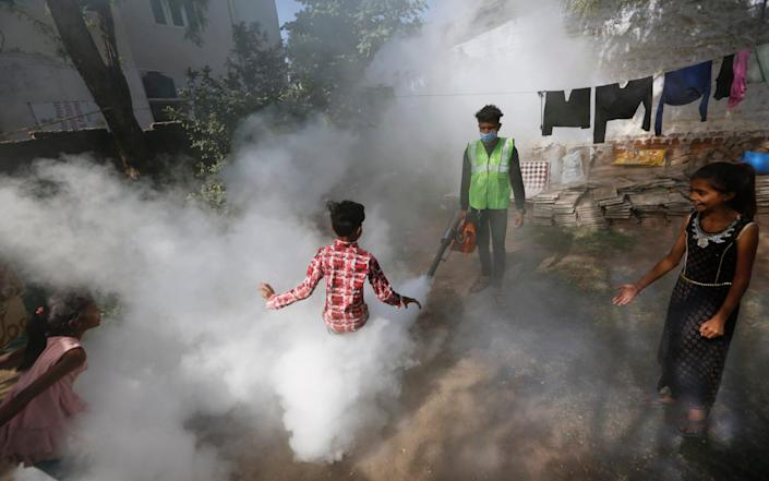 A boy plays smoke from fumigation being carried out by a municipal worker at a residential area in Ahmedabad, India - AP