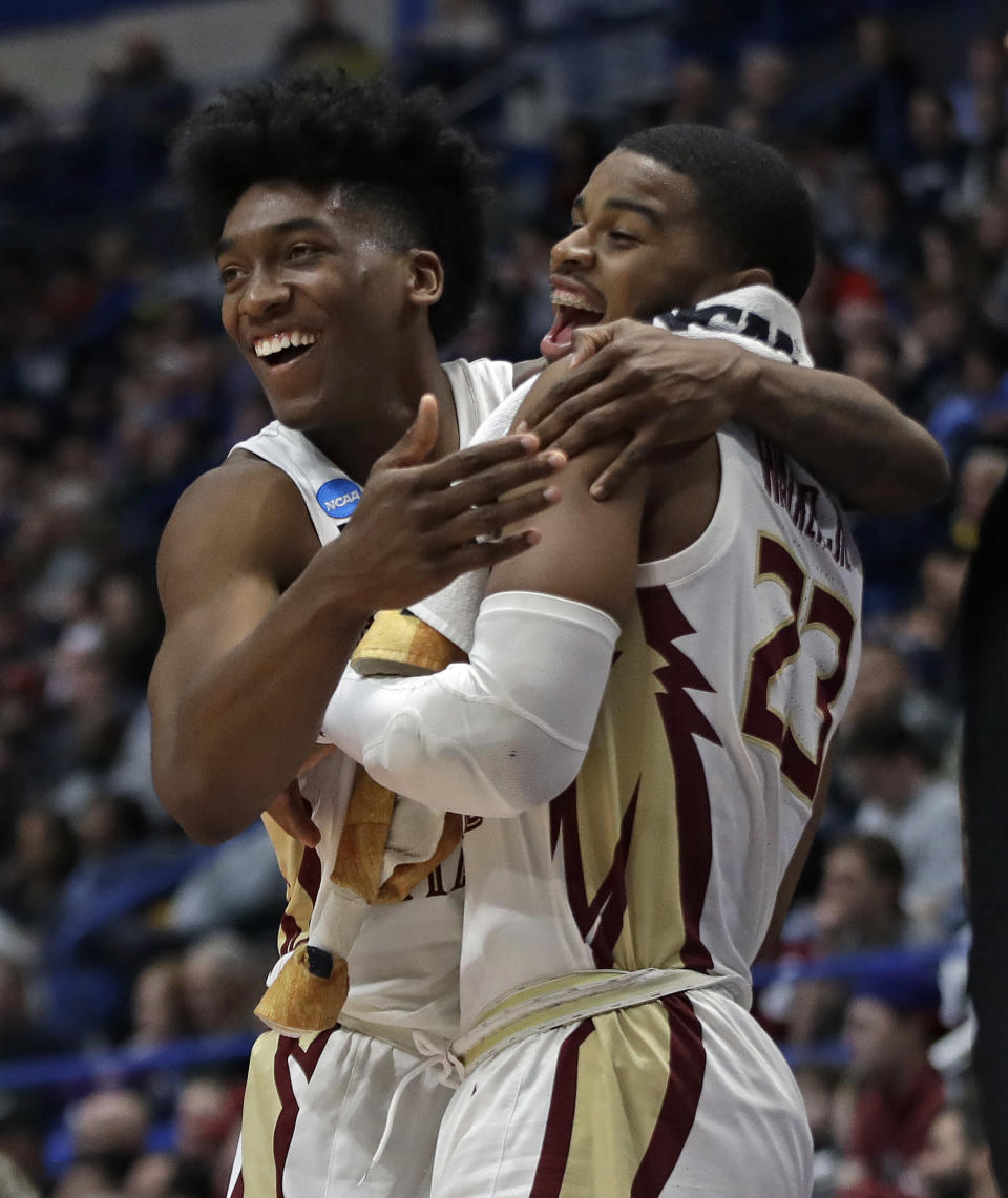 Florida State's Terance Mann, left, and M.J. Walker celebrate at the bench during the second half of a second round men's college basketball game against Murray State in the NCAA Tournament, Saturday, March 23, 2019, in Hartford, Conn. Florida State won 90-62. (AP Photo/Elise Amendola)