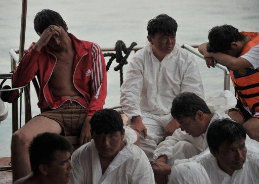 Asylum-seeker survivors are seen onboard an Indonesian rescue boat at Merak seaport
