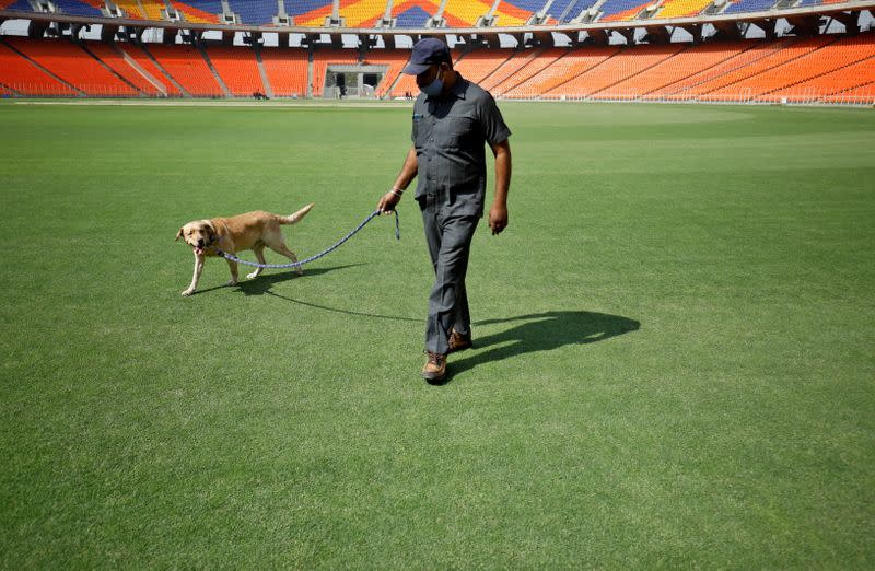 A member of a bomb disposal squad from Gujarat Police walks with a sniffer dog to scan the field at Sardar Patel Gujarat Stadium, in Ahmedabad