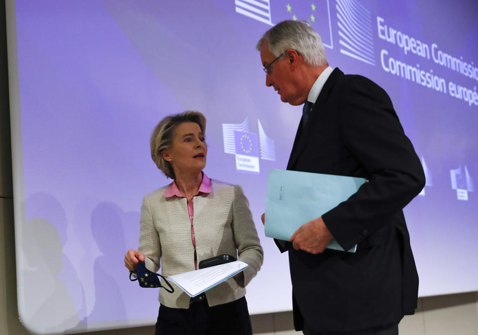 European Commission's Head of Task Force for Relations with the United Kingdom Michel Barnier, right, speaks with European Commission President Ursula von der Leyen after addressing a media conference on Brexit negotiations at EU headquarters in Brussels, Thursday, Dec. 24, 2020. (AP Photo/Francisco Seco, Pool)