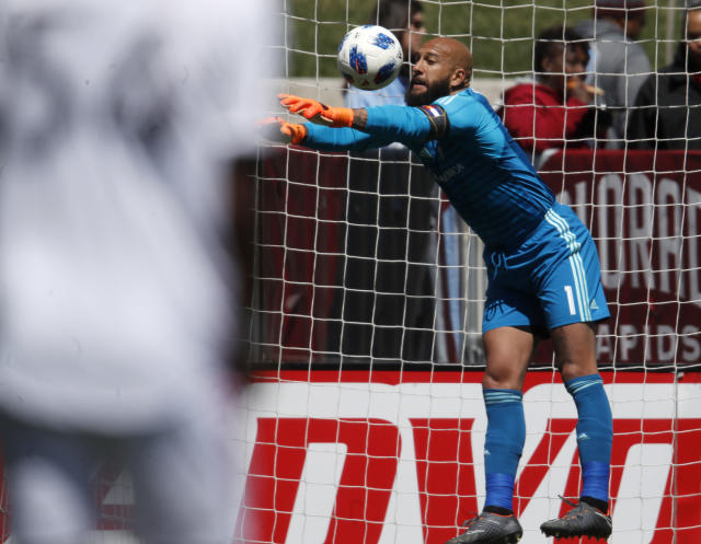 Colorado Rapids goalkeeper Tim Howard deflects a shot while facing Toronto FC in the first half of an MLS soccer match Saturday, April 14, 2018, in Commerce City, Colo. (AP Photo/David Zalubowski)