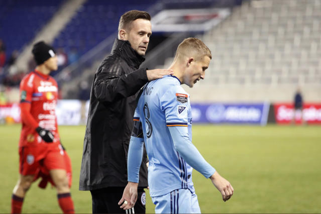 New York City FC head coach Ronny Deila, center, congratulates New York City FC captain and midfielder Alexander Ring, right, after NYC FC defeated San Carlos 1-0 in a CONCACAF Champions League round of 16 soccer match, Wednesday, Feb. 26, 2020, in Harrison, N.J. A San Carlos player leaves the field at left. (AP Photo/Kathy Willens)