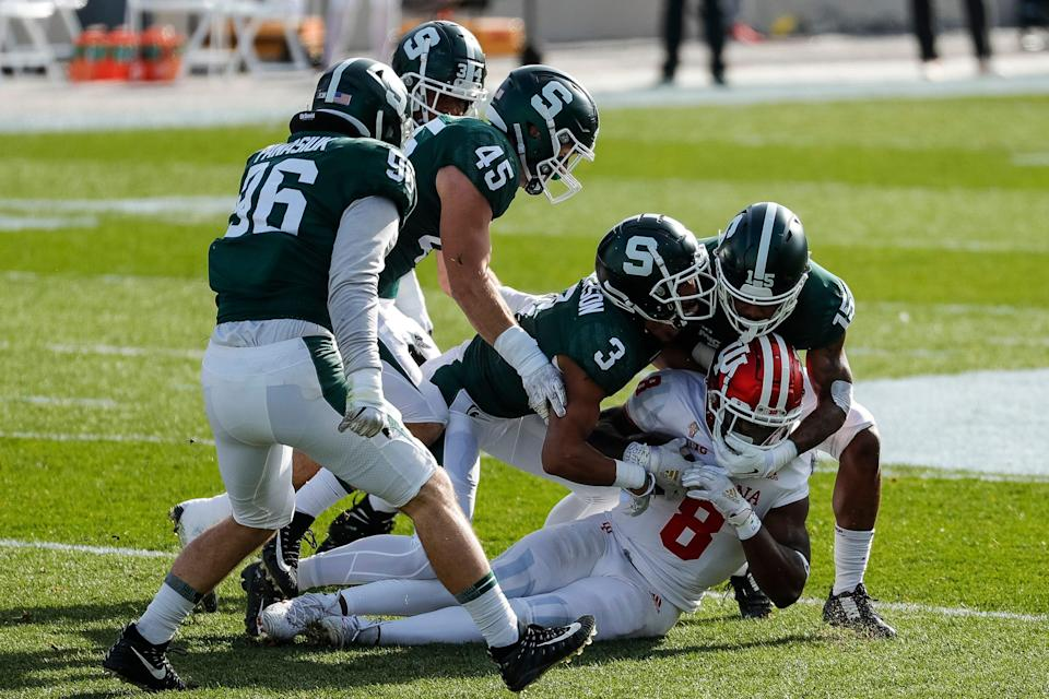 Indiana running back Stevie Scott III is stopped by Michigan State safety Xavier Henderson, left, and cornerback Angelo Grose and during the first half at Spartan Stadium in East Lansing, Saturday, Nov. 14, 2020.