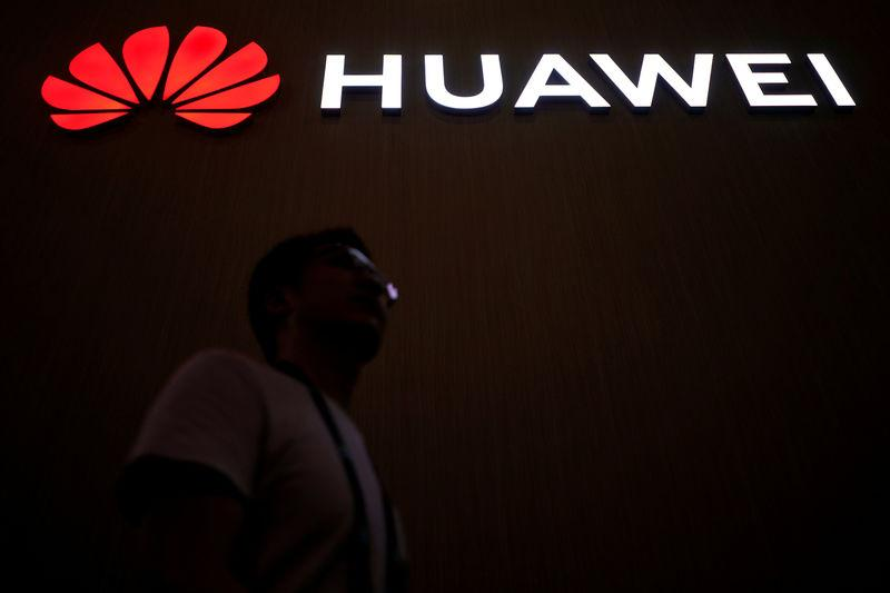 A man walks past a sign board of Huawei at CES (Consumer Electronics Show) Asia 2018 in Shanghai