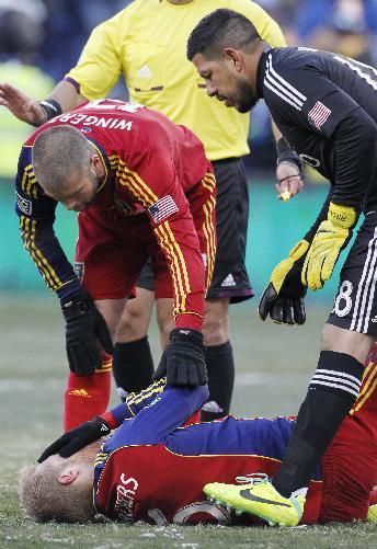 Real Salt Lake defender Chris Wingert (17) and goalkeeper Nick Rimando (18) check on defender Nat Borchers (6) after he got hit in the face with the ball during the first half of the MLS Cup final soccer match against Sporting Kansas City in Kansas City, Kan., Saturday, Dec. 7, 2013. (AP Photo/Colin E. Braley)