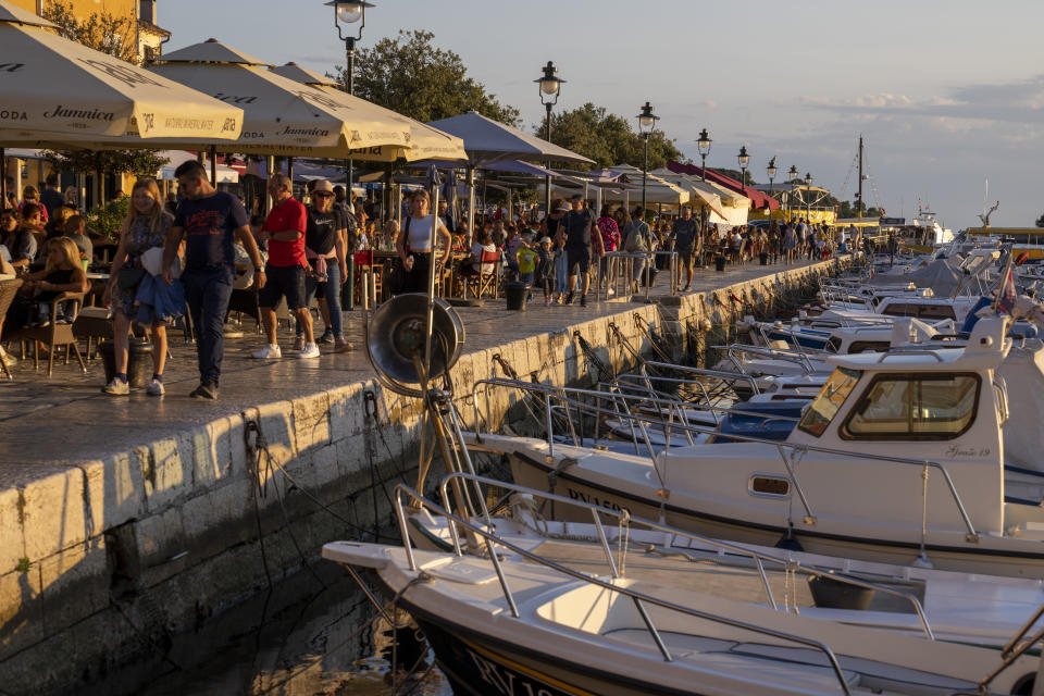 Holidaymakers walk by the harbor, in the Adriatic town of Rovinj, Croatia, Friday, Aug. 27, 2021. Summer tourism has exceeded even the most optimistic expectations in Croatia this year. Beaches along the country's Adriatic Sea coastline are swarming with people. Guided tours are fully booked, restaurants are packed and sailboats were chartered well in advance. (AP Photo/Darko Bandic)
