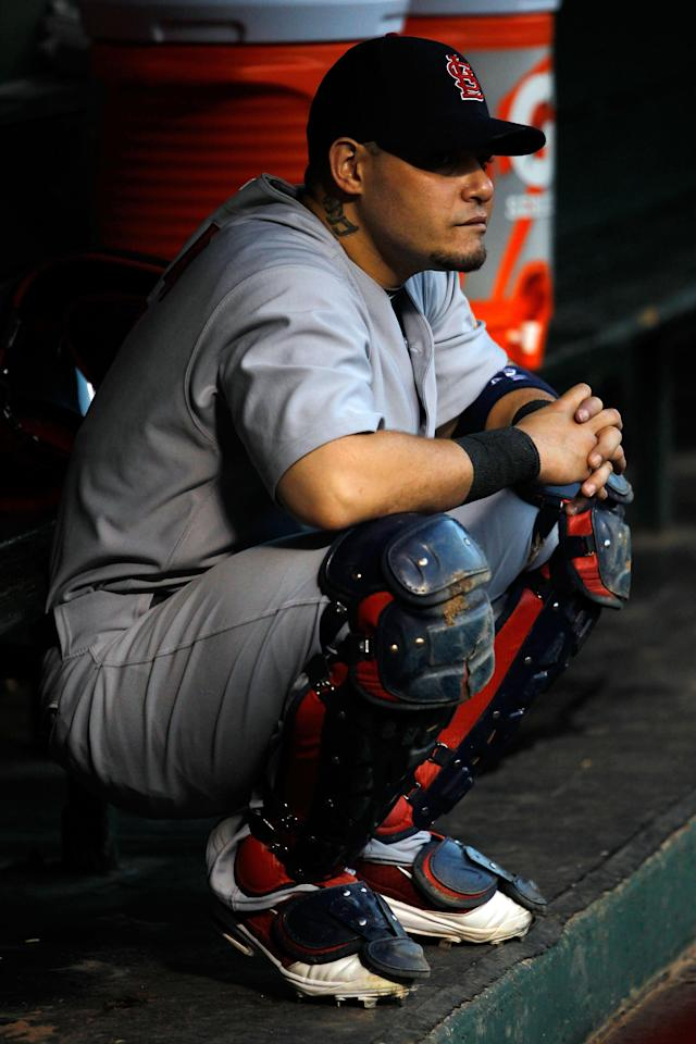 ARLINGTON, TX - OCTOBER 24: Yadier Molina #4 of the St. Louis Cardinals croutches in the dugout prior to Game Five of the MLB World Series against the Texas Rangers at Rangers Ballpark in Arlington on October 24, 2011 in Arlington, Texas. (Photo by Tom Pennington/Getty Images)