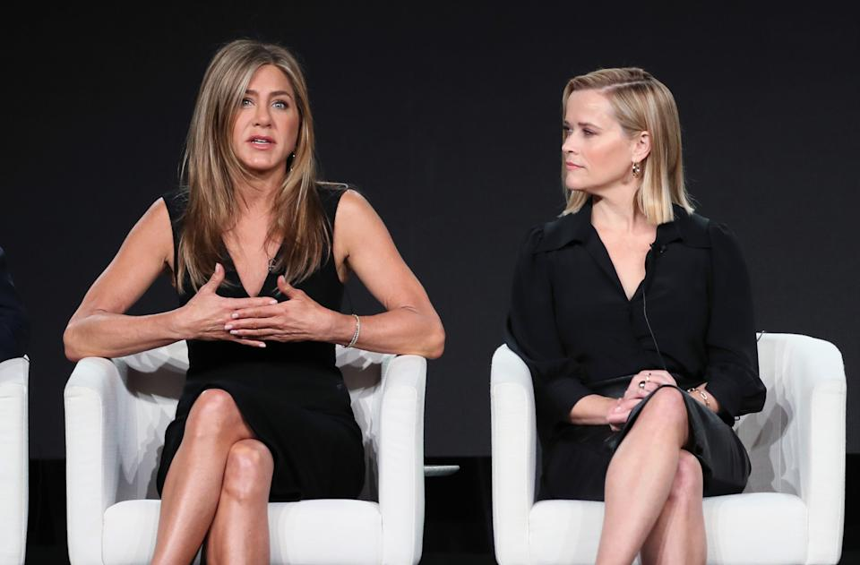 """PASADENA, CALIFORNIA - JANUARY 19: Jennifer Aniston (L) and Reese Witherspoon of """"The Morning Show"""" speak on stage during the Apple TV+ segment of the 2020 Winter TCA Tour at The Langham Huntington, Pasadena on January 19, 2020 in Pasadena, California. (Photo by David Livingston/Getty Images)"""