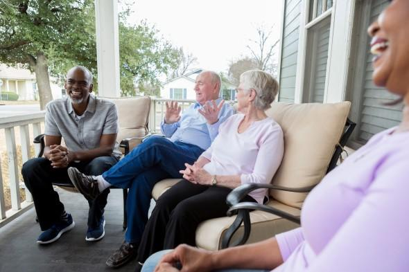 Neighbors chatting on a porch - Getty Images