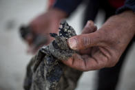 A local fisherman who goes by the name Jumbo holds tar that washed on to the docks from an oil spill in the Mediterranean Sea, in the Israeli Arab village of Jisr al-Zarqa, Israel, Thursday, Feb. 25, 2021. After weathering a year of the coronavirus pandemic, an oil spill in the Mediterranean whose culprits remain at large delivered another blow for the fishermen of Jisr al-Zarqa. (AP Photo/Ariel Schalit)