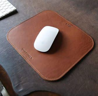 """This Alabama-based Amazon Handmade shop specializes in handmade leather goods. Find this <a href=""""https://amzn.to/2NHHonC"""" rel=""""nofollow noopener"""" target=""""_blank"""" data-ylk=""""slk:personalized fine leather mouse pad"""" class=""""link rapid-noclick-resp""""> personalized fine leather mouse pad</a> for $24."""