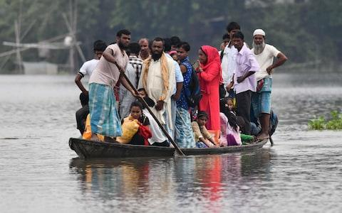 Indian villagers travel by boat through floodwaters in Morigoan district, in India's northeastern state of Assam.  - Credit: Biju Boro/AFP