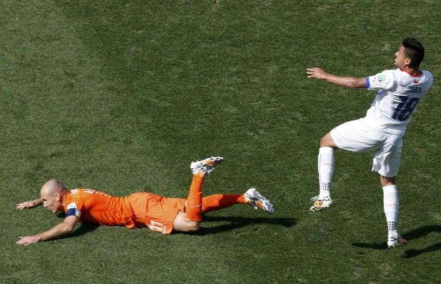 Arjen Robben of the Netherlands (L) falls in front of Chile's Gonzalo Jara during their 2014 World Cup Group B soccer match at the Corinthians arena in Sao Paulo June 23, 2014. REUTERS/Paulo Whitaker (BRAZIL - Tags: SOCCER SPORT WORLD CUP)