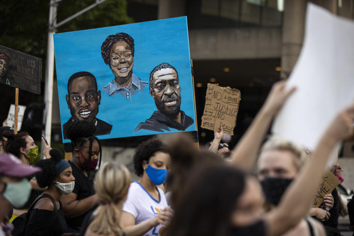 Protesters carry a painting of (L-R) Ahmaud Arbery, Breonna Taylor and George Floyd while marching on June 5, 2020 in Louisville, Kentucky. (Photo by Brett Carlsen/Getty Images)