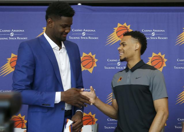 Phoenix Suns' Deandre Ayton, left, and Elie Okobo, right, of France, slap hands after the team introduced its new players after the NBA basketball draft Friday, June 22, 2018, in Phoenix. (AP Photo/Ross D. Franklin)