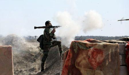 An Iraqi soldier launches a rocket-propelled grenade towards Islamic State militants, west of Falluja