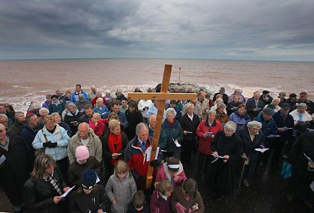 Members of the Churches Together in Sidmouth take part in their annual Good Friday Walk of Witness procession on the seafront in Sidmouth, England.