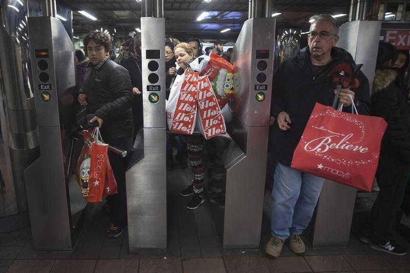 Shoppers enter the 34th Street subway station with packages on Black Friday in New York
