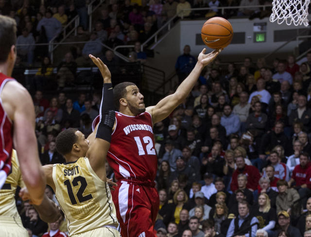 Wisconsin's Traevon Jackson (12) moves past Purdue's Bryson Scott (12) to score in the second half of an NCAA college basketball game, Saturday, Jan. 25, 2014, in West Lafayette, Ind. Wisconsin defeated Purdue 72-58. (AP Photo/Doug McSchooler)