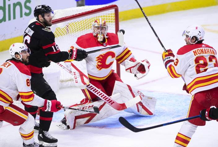 Ottawa Senators left wing Austin Watson (16) gets his stick on a flying puck as Calgary Flames goaltender David Rittich (33) keeps an eye on it during second period NHL hockey action in Ottawa on Monday, March 1, 2021. (Sean Kilpatrick/The Canadian Press via AP)