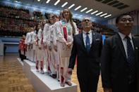 In a photo taken on September 21, 2017 team members from North Korea (C) and Russia (R) stand on the podium of during the medal ceremony of womens team event of the 20th ITF World Taekwondo Championships in Pyongyang