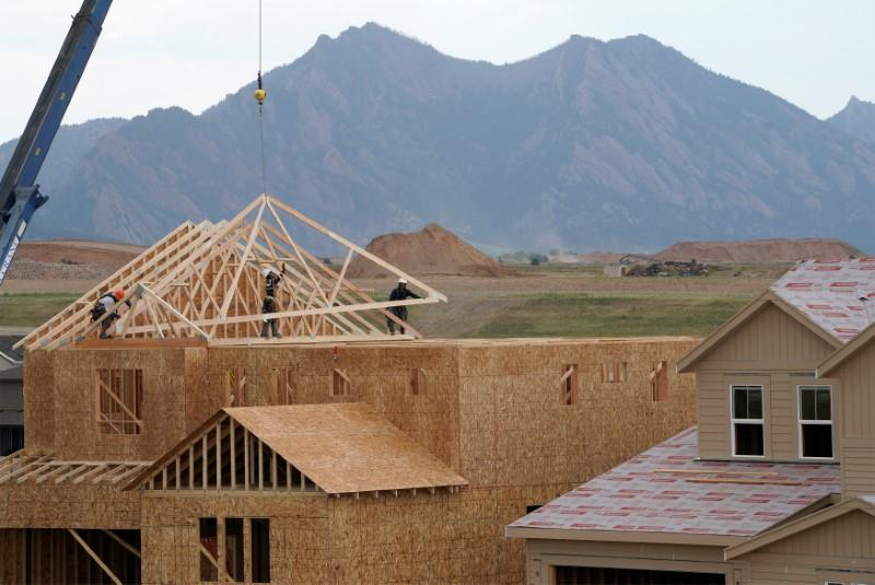 Workers install roof trusses onto a new house in Arvada