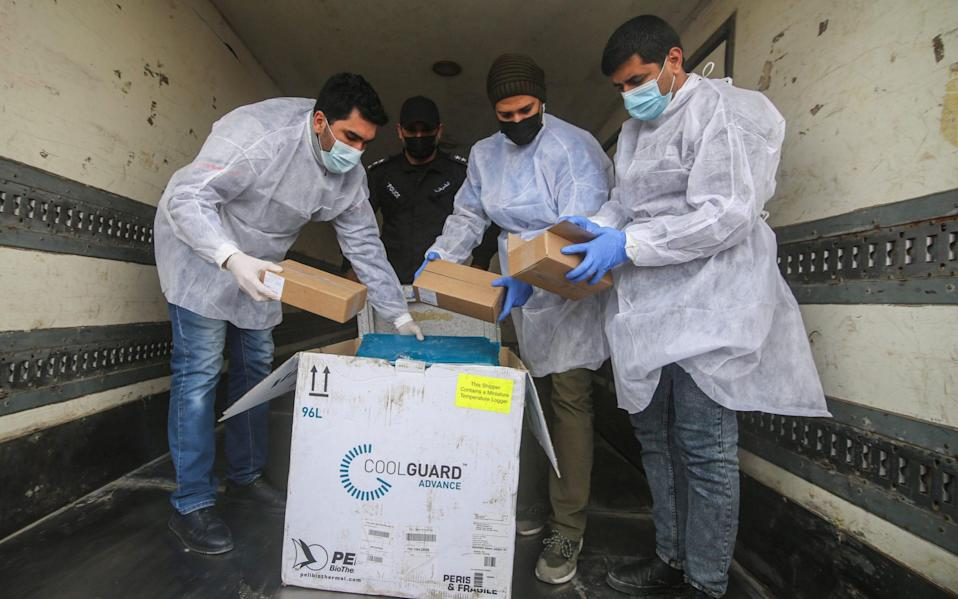 Palestinian workers unload the first shipment of Sputnik V Covid-19 vaccines from Israel, on the Palestinian side of the Kerem Shalom border crossing, south of Rafah, Gaza, on Wednesday Feb. 17. Israel has approved the shipment of Russian-made Sputnik coronavirus vaccine to Gaza - Ahmad Salem/Bloomberg