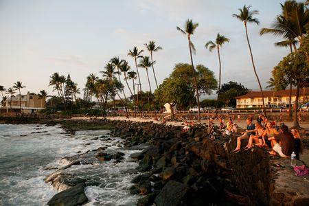 Tourists and locals watch the sunset from White Sands Beach Park in Kailua-Kona, on Hawaii's Big Island, January 31, 2016. REUTERS/Canice Leung