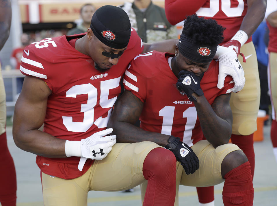 Eric Reid (35), taking a knee with Marquise Goodwin (11) during the performance of the national anthem in November, has filed a grievance against the league. (AP)