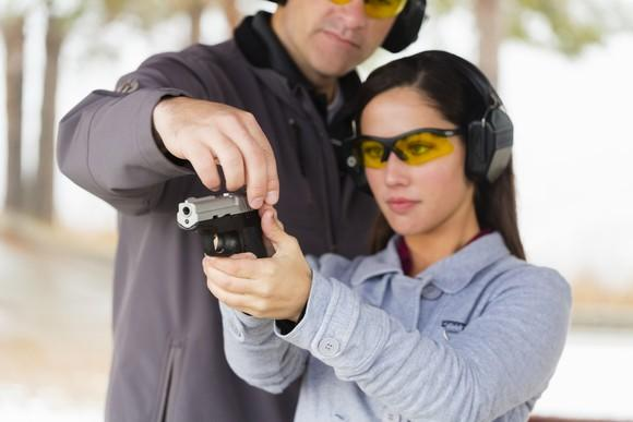 Woman holding pistol and wearing safety glasses and earmuffs. Another person holds the top of the firearm