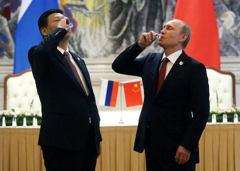 Putin regularly opens his drinks cabinet to visiting leaders - Credit: GETTY